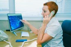De mooie makelaar die van de meisjesvoorraad op de telefoon in het bureau spreken stock foto's