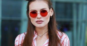 De mooie manier in rode zonnebril stelt aan de camera met vóór een modern glasgebouw Het jonge transsexueel kijken stock footage