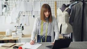 De mooie manierontwerper trekt kledingsschetsen voor haar nieuwe klereninzameling en werkt met laptop licht stock videobeelden