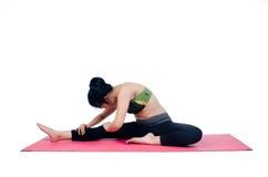 De mooie mat van de vrouwen binnen uitoefenende gebruikende roze yoga Stock Foto's
