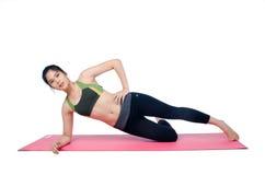 De mooie mat van de vrouwen binnen uitoefenende gebruikende roze yoga Royalty-vrije Stock Afbeelding