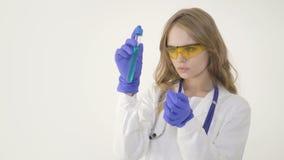 De mooie medische arts in beschermende glazen werkt met een reageerbuis stock footage