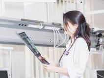 De mooie meisje arts in een witte laag onderzoekt Röntgenstraalfoto van de patiënt om het probleem te identificeren Professioneel royalty-vrije stock afbeelding