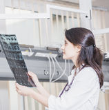 De mooie meisje arts in een witte laag onderzoekt Röntgenstraalfoto van de patiënt om het probleem te identificeren Professioneel stock foto