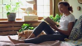 De mooie meisje gemengde rasstudent leest boek en streelt huisdierenhond uitdrukkend liefde en zorgzitting op bed in stock videobeelden