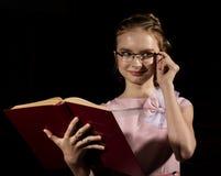 De mooie meisje status en leest boek over donkere achtergrond stock foto's