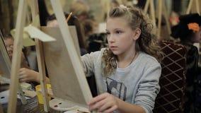 De mooie meisjes blonde tiener schildert het schilderen in een kunstacademie stock video