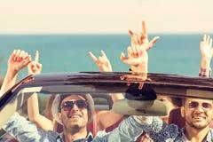 De mooie meisjes die van de partijvriend in een auto op het gelukkige strand dansen Stock Foto