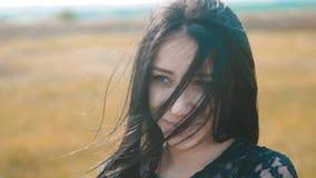 De mooie meisjes donkerbruine wind ontwikkelt de langzame geanimeerde video van het haarportret de sterke wind van het donkerbrui stock videobeelden