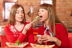 De mooie meisjes eten sushibroodjes bij sushibar. Royalty-vrije Stock Afbeelding