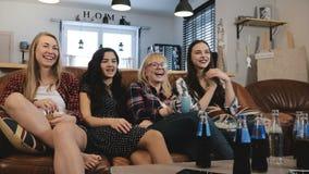 De mooie meisjes letten en bespreken op film op TV De gelukkige glimlachende vrouwelijke vrienden genieten samen van de langzame  stock video