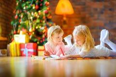 De mooie meisjes liggen op de vloer dichtbij de Kerstboom en schrijven een brief aan Kerstman stock afbeeldingen