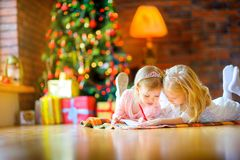 De mooie meisjes liggen op de vloer dichtbij de Kerstboom en schrijven een brief aan Kerstman royalty-vrije stock foto's