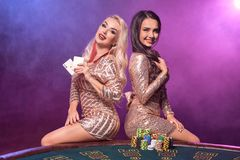 De mooie meisjes met perfecte kapsels en heldere samenstelling stellen status bij een het gokken lijst Casino, pook stock foto's