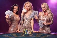De mooie meisjes met perfecte kapsels en heldere samenstelling stellen status bij een het gokken lijst Casino, pook royalty-vrije stock foto
