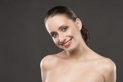 De mooie meisjes naakte schouders glimlacht op een grijze achtergrond Royalty-vrije Stock Fotografie