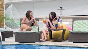 De mooie meisjes in de waterpijp van de zwempakkenrook en drinken cocktails dichtbij pool stock video