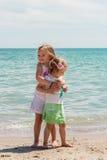 De mooie meisjes (zusters) spelen op het strand Stock Foto