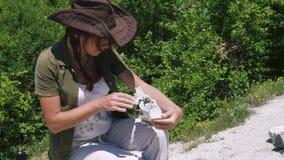 De mooie meisjesarcheoloog inspecteert de schedel van binnenlandse schapen of een geit dichtbij de regelingen van oude mensen stock video