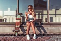 De mooie meisjesatleet in vrijetijdskleding, de zomerstad, skateboard, longboard, zit handtelefoon, leest sociale toepassing royalty-vrije stock foto