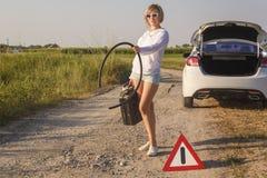 De mooie meisjesbestuurder in de auto liep uit brandstof en zij stemt over een landelijke weg wachtend op hulp met een lege brand royalty-vrije stock fotografie