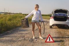 De mooie meisjesbestuurder in de auto liep uit brandstof en zij stemt over een landelijke weg wachtend op hulp met een lege brand stock foto