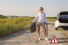 De mooie meisjesbestuurder in de auto liep uit brandstof en zij stemt over een landelijke weg wachtend op hulp met een lege brand stock afbeelding