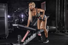 De mooie meisjesbodybuilder, voert oefening met domoren, in donkere gymnastiek uit royalty-vrije stock foto's
