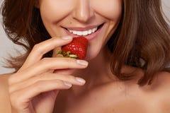 De mooie meisjesglimlach en eet rode aardbei Royalty-vrije Stock Afbeeldingen