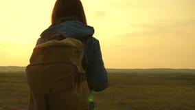 De mooie meisjesreiziger met een rugzak gaat te voet bij zonsondergang Het Meisje van de toerist Concept in de campagne vrijheid  stock videobeelden