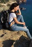 De mooie meisjesreiziger zit op rotsrand met rugzak Stock Afbeelding