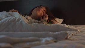 De mooie meisjesslaap in slaapkamer met licht op toen wekt plotseling en glimlacht stock video