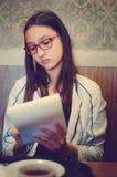 De mooie meisjeszitting in een koffie en schrijft in een notitieboekje Gekleurde foto stock afbeelding