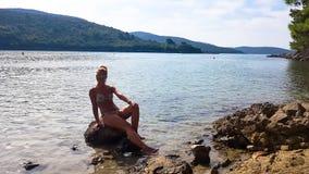 De mooie meisjeszitting op een rots en geniet van zonnebadend royalty-vrije stock foto's