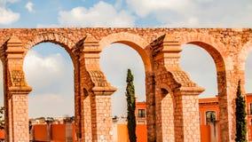 De mooie mening van baksteen en steen overspant in een oranje kleur van een oude arena stock foto