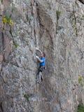 De mooie mens beklimt een hoge berg stock fotografie