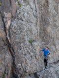 De mooie mens beklimt een hoge berg stock foto