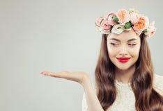 De mooie Model Open Hand van Woman Showing Empty op Witte Achtergrond Mooi Meisje met Duidelijke Huid, Krullend Haar, Make-up en  stock afbeeldingen