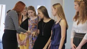 De mooie modellentribune in lijn en toont manicure aan hun leraar aan stock footage