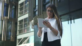 De mooie modieuze belangrijkste vrouwenbankier gebruikt tablet die zich op stedelijke de bouwachtergrond bevinden stock videobeelden