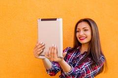 De mooie modieuze glimlachende vrouwen maken selfie door tablet Oranje Achtergrond Exemplaar-ruimte Stock Afbeelding