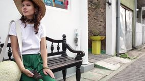 De mooie modieuze vrouw in een strohoed zit op de bank bij de straat stock video