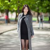 De mooie modieuze vrouw in zwarte kleding en de comfortabele trenchcoat lopen in stadspark De lente openluchtlevensstijl Het gelu stock foto's