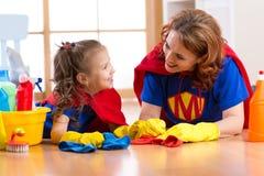 De mooie moeder en de leuke jong geitjedochter kleedden zich als superheroes Vrouw en kind klaar aan het schoonmaken van het huis stock afbeelding