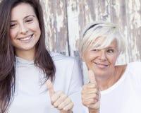 De mooie moeder en de volwassen dochter maken het teken Stock Afbeeldingen