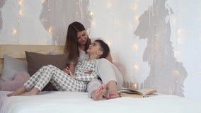 De mooie moeder kust haar baby terwijl het zitten op het bed Het kind ligt op zijn moeder` s overlapping stock video