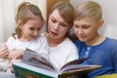 De mooie moeder leest een boek aan haar jonge kinderen De zuster en de broer luisteren aan een verhaal royalty-vrije stock foto