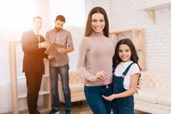 De mooie moeder met haar dochter houdt sleutels met sleutelring in vorm van huis stock foto