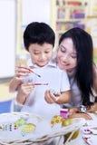 De mooie moeder onderwijst zoon hoe te om paasei te schilderen Stock Afbeeldingen
