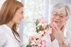 De mooie moeder van de vrouwengroet met bloemen het glimlachen Stock Afbeelding